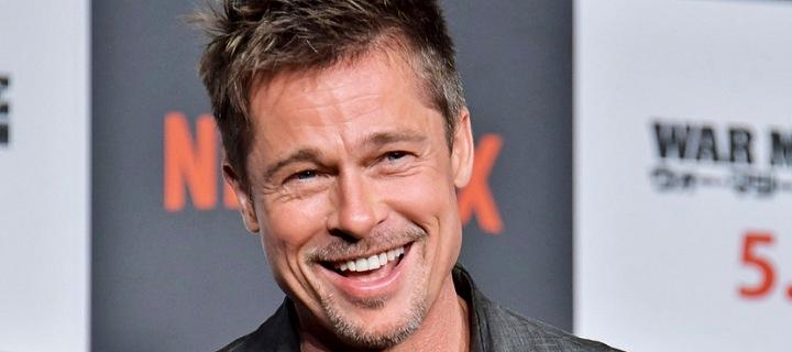 Brad Pitt v bundě a s mikrofonem v ruce