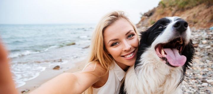 Usměvavá dívka na pláži dělající si selfie se svým psem