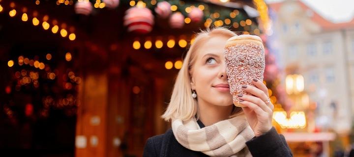 Dívka na vánočních trzích s trdelníkem.