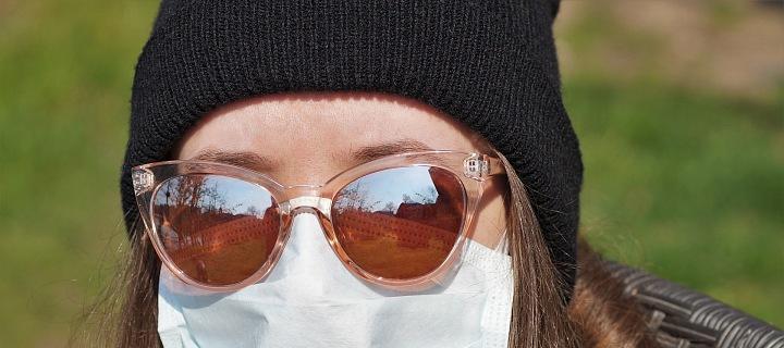 Dívka s rouškou a slunečními brýlemi