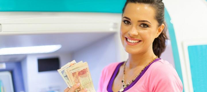 Dívka v růžovém triku stojící u bankomatu s penězi v ruce