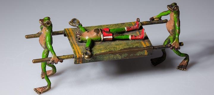 Bronzoví žabáci nesou na nosítkách opilého žabáka.