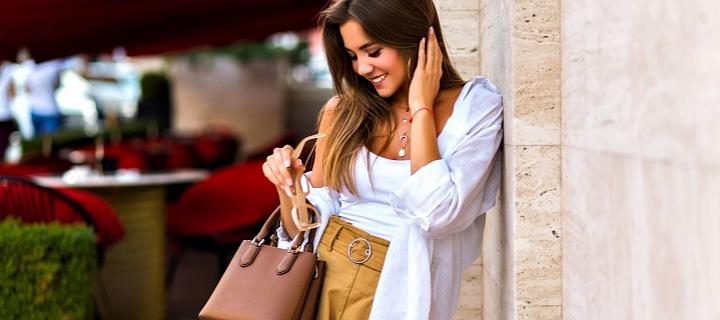 Žena stojí na ulici s kabelkou.