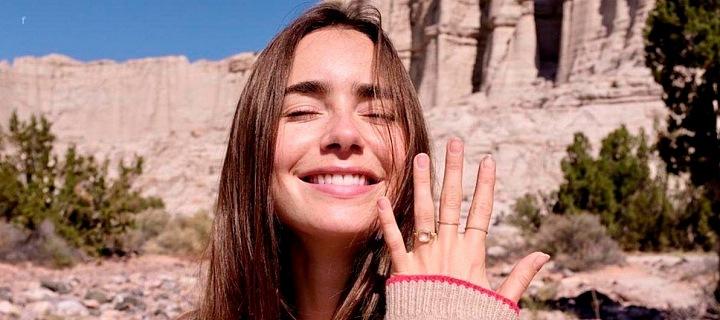 Lily Collins, na ruce zásnubní prsten s růžovým diamantem.
