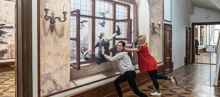Návštěvnice muze se fotí před 3D obrazem pražské defenestrace