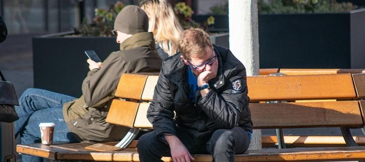 Smutný muž sedící na lavičce.