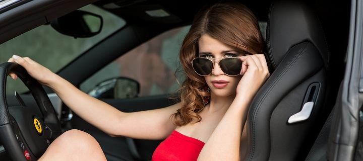 Krásná dívka v červených sexy šatech pózuje ve Ferrari 458 Italia