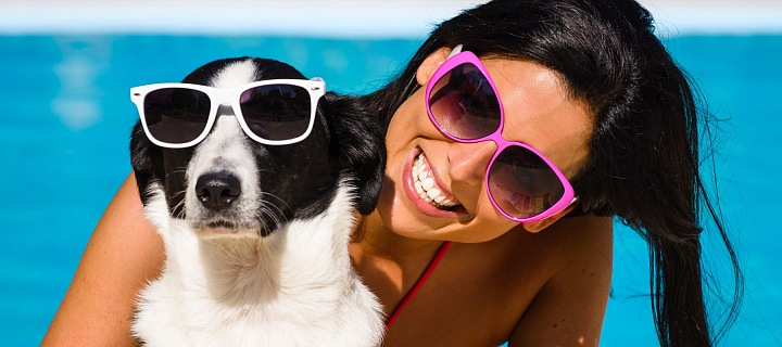 I se psím mazlíčkem se dá bárzdit svět. Dívka se psem u bazénu, oba ve slunečních brýlích.