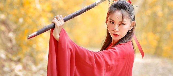 Krásná Mladá čínská dívka v červeném hábitu s mečem