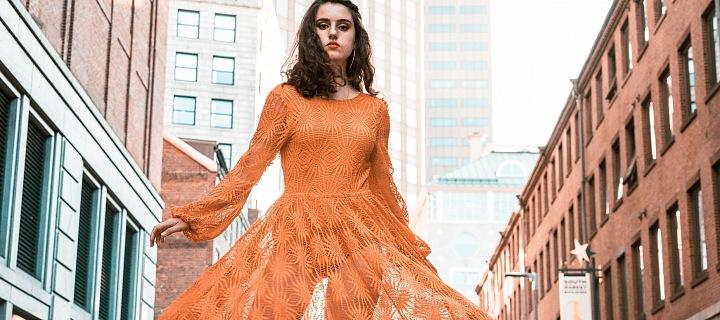 Žena v oranžových šatech ve městě