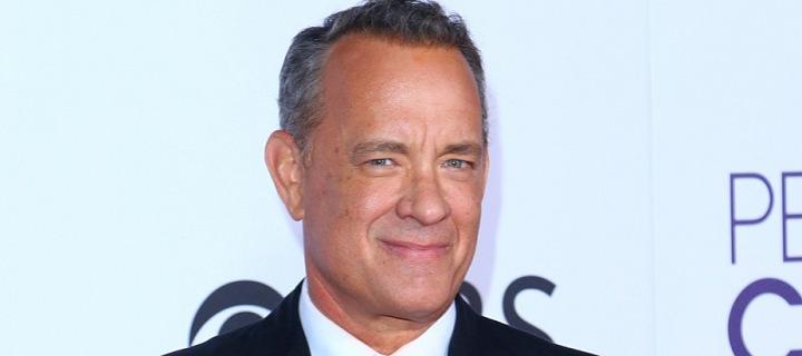 Tom Hanks stojí v tmavém obleku