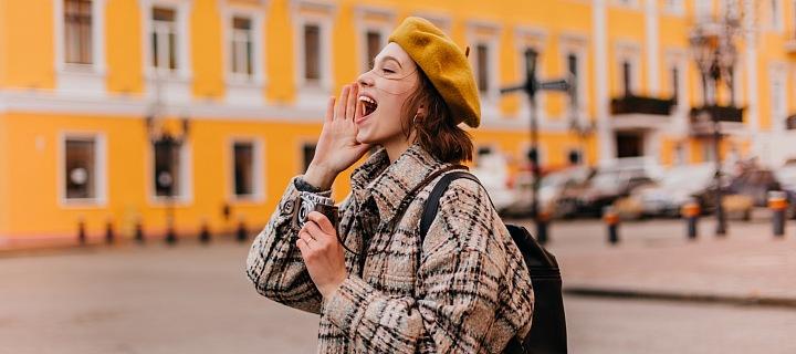 Žena křičí na své kamarády na ulici.