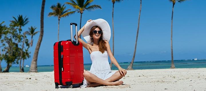 Žena na pláži s kufrem