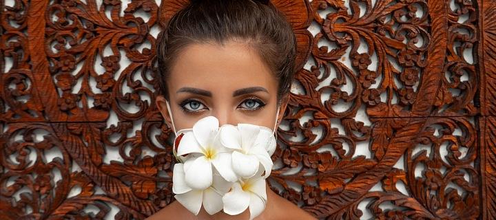 Žena s květinami na ústech namísto roušky.