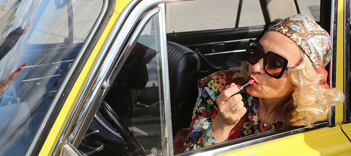 Žena se líčí v retro autě.