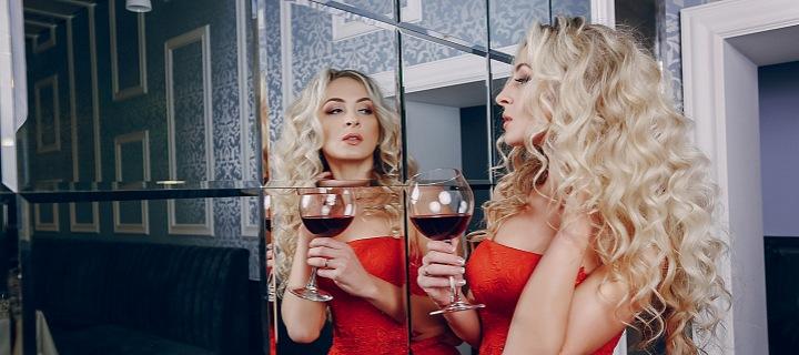 Žena se sklenicí vína před zrcadlem.