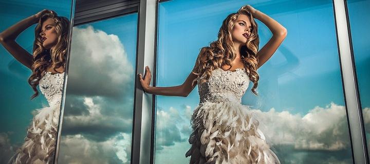 Žena stojí v bílých šatech s peříčky u okna