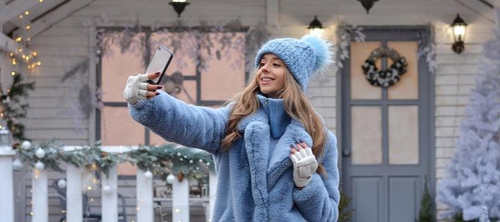 Žena si u vánočního domu dělá selfie.