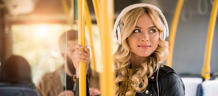 Žena v autobuse se sluchátky na uších