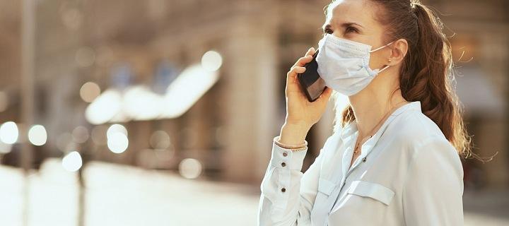 Žena s rouškou telefonuje na ulici