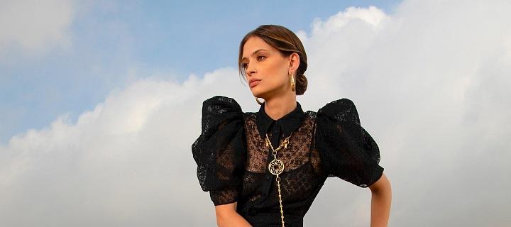 Žena v černých šatech sedící na kameni