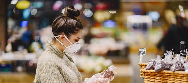 Žena v roušce nakupuje.