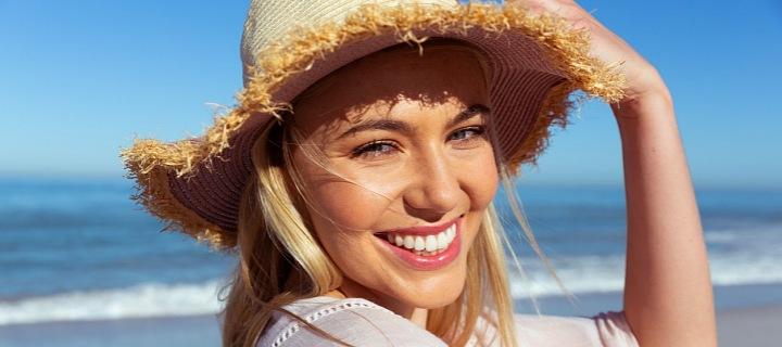 Žena ve slamáku na pláži