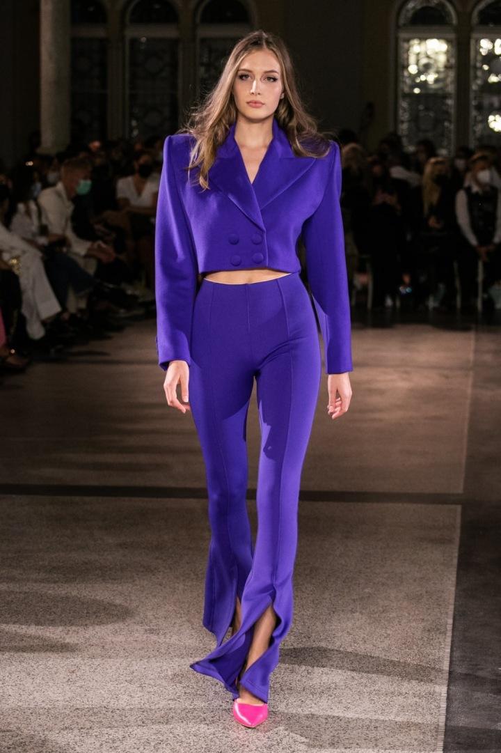 Modelka má na sobě fialový kostýmek od Vandy Jandy