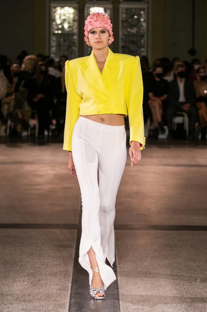 Modelka má na sobě žlutý kabátek a bílé kalhoty od Vandy Jandy