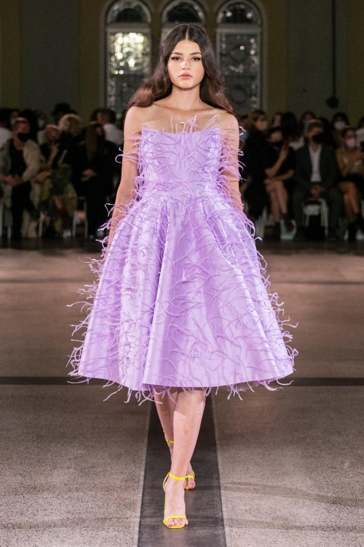 Modelka má na sobě kratší šaty pošité pírky od Vandy Jandy