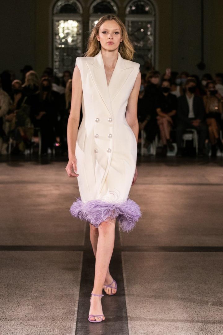 Modelka má na sobě bílé šaty s pírky od Vandy Jandy