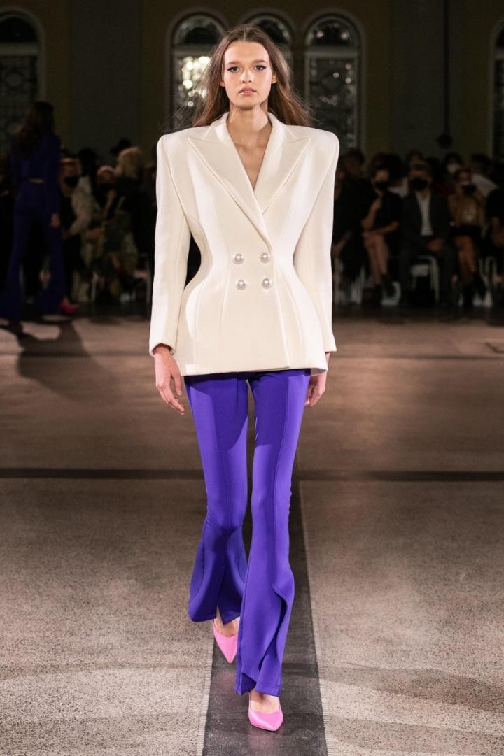 Modelka má na sobě fialovo-bílý outfit od Vandy Jandy
