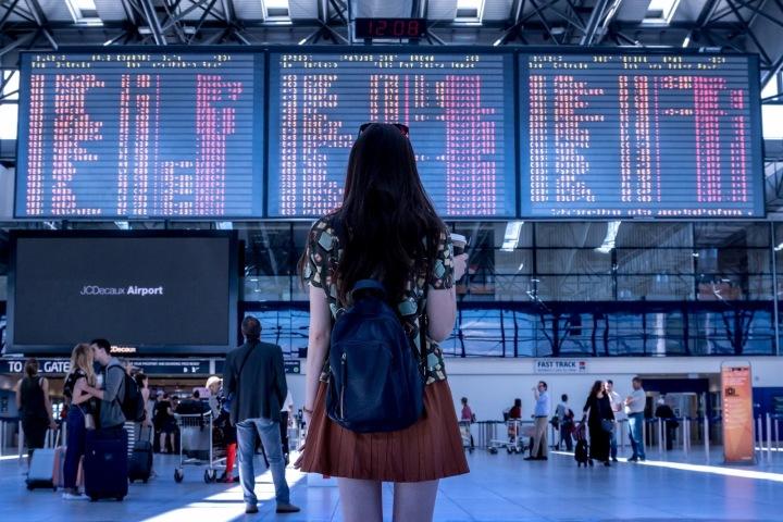 Dívka na letišti sledující tabuli odletů
