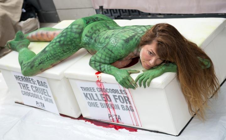 """Žena má na sobě namalovaný """"krokodýlí"""" vzor a pod sebou kaluž krve."""