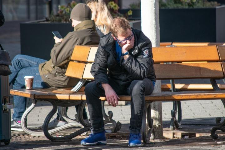 Zoufalý muž sedící na lavičce