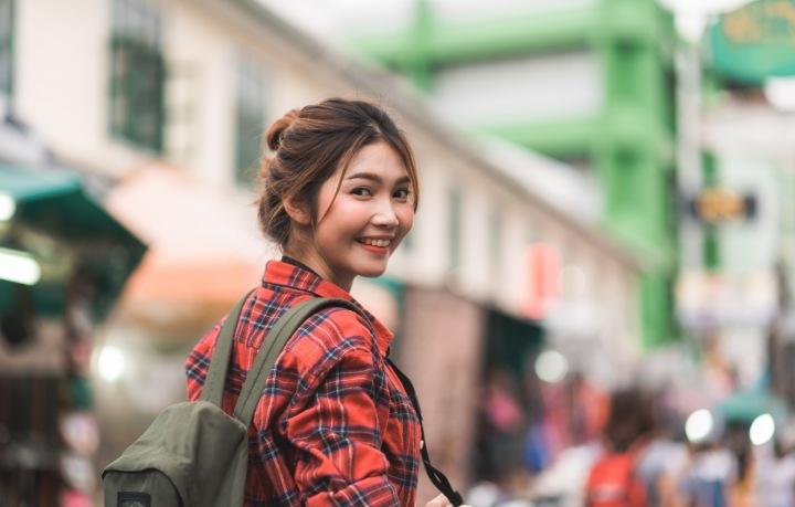 Asiatka v kostkované košili stojí na ulici a usmívá se