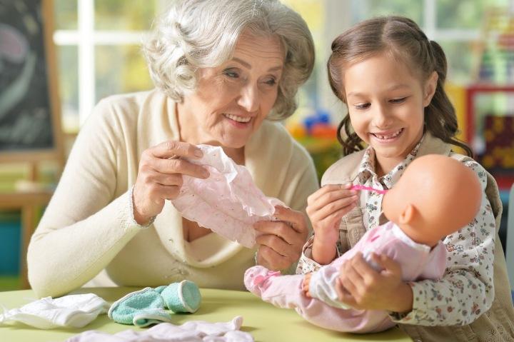 Babička a vnučka si hrají s panenkou.
