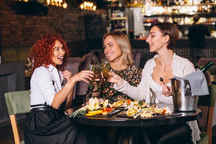 Ženy si přiťukávají v baru.