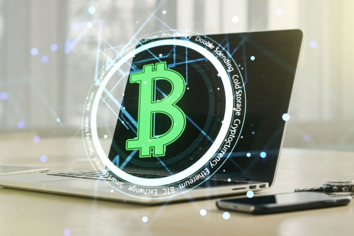 Symbol bitcoinu s laptopem v pozadí