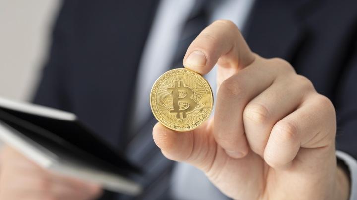 Muž drží v ruce minci.