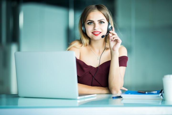 Žena u počítače se sluchátky na uších.