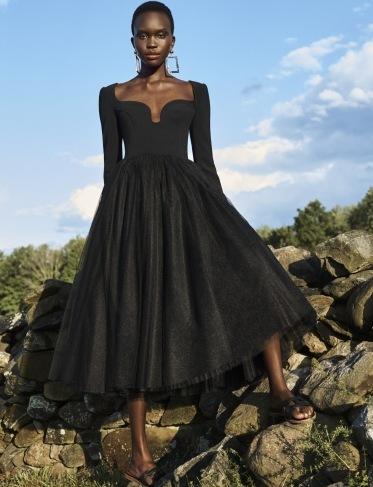 Žena v černých midi šatech