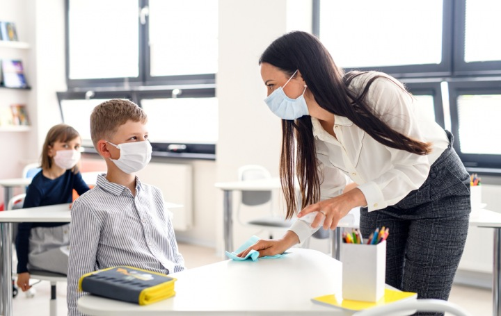 Chlapec sedí ve třídě s rouškou. Ochranu úst má i jeho učitelka