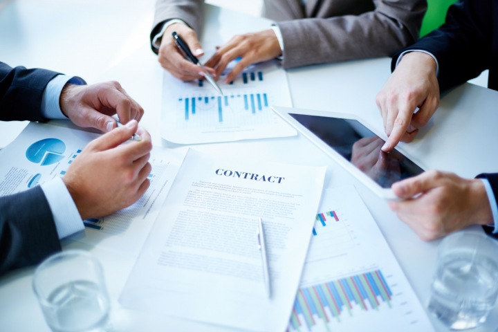 Kontrola osobních údajů. Ruce tří mužů za stolem s daty a grafy