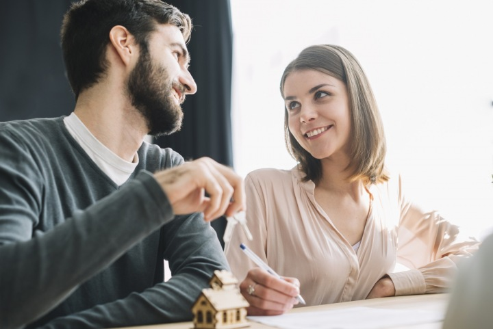 Mladý pár se na sebe zamilovaně dívá u podpisu smlouvy na hypotéku