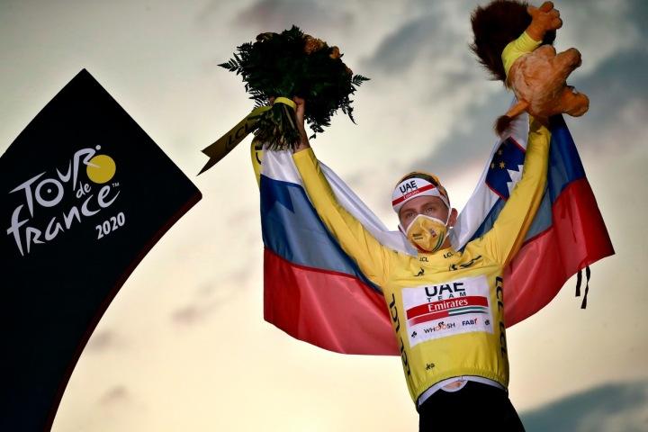Cyklista Pogačar stojí ve žlutém dresu, nad hlavou drží květiny a plyšáka