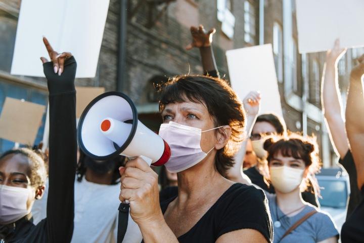 Lidé demonstrují v rouškách.