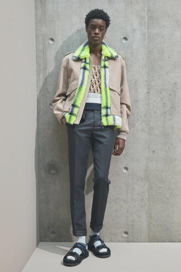 Muž v šedých kalhotách a béžové bundě Dior
