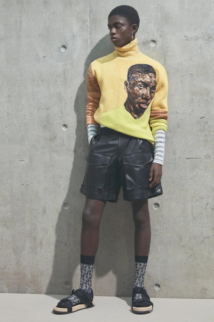 Muž v šortkách a žlutém svetru Dior