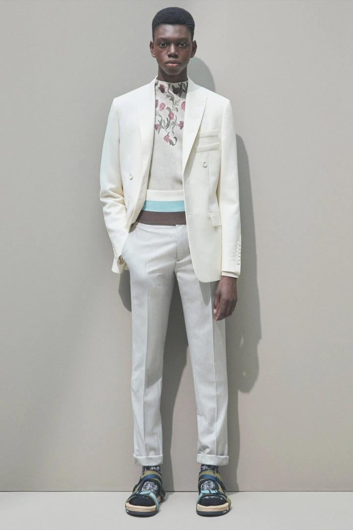 Muž v bílém obleku Dior